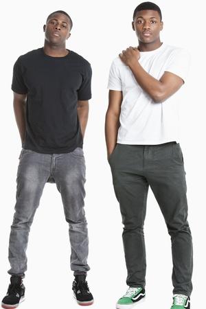 hombres jovenes: Retrato de dos hombres jóvenes en casuals sobre fondo gris