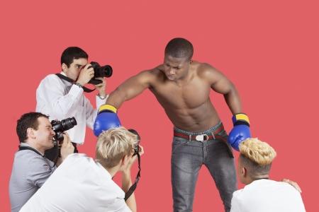 arroganza: Paparazzi scattare fotografie di boxer maschio su sfondo rosso