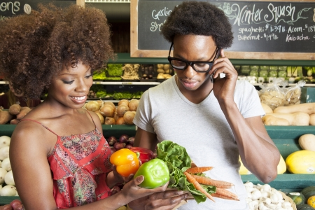 african ethnicity: Young African American couple buying vegetables at supermarket