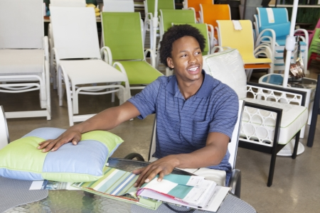 seating furniture: Male African American salesperson working in garden furniture store