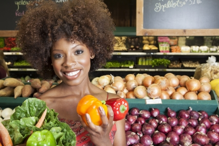 african ethnicity: African American woman holding bell peppers and vegetables at supermarket