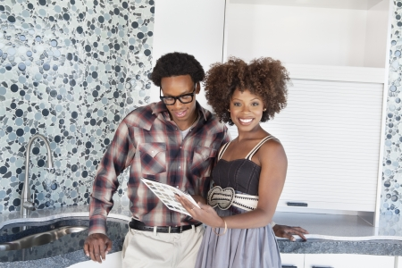 decisionmaking: Portrait of young African American couple with color swatches in new kitchen
