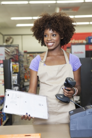 checkout stand: Portrait of an African American female store clerk standing at checkout counter