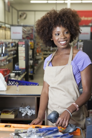 checkout stand: Portrait of an African American female store clerk standing at checkout counter scanning item