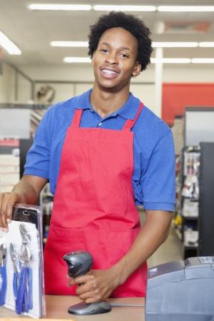 checkout stand: Portrait of an African American male store clerk standing at checkout counter