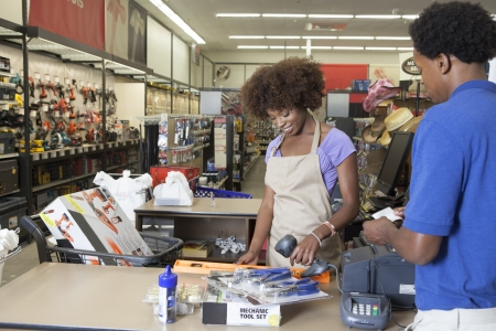 checkout stand: Portrait of an African American female store clerk standing at checkout counter scanning item serving male customer