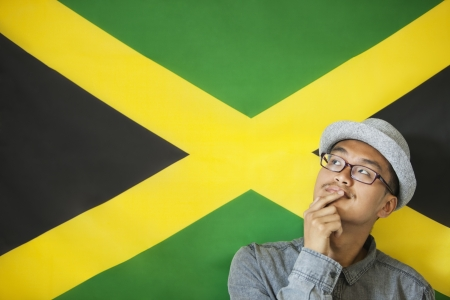 jamaican man: Thoughtful man against Jamaican flag LANG_EVOIMAGES