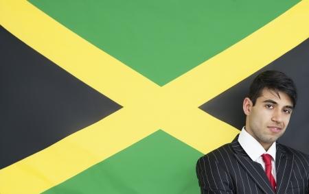 jamaican adult: Portrait of a confident businessman against Jamaican flag