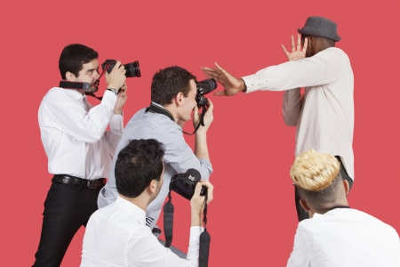 peo: Young male celebrity shielding face from photographers over red background