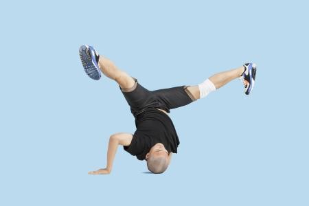 legs spread: Bailar�n de sexo masculino que hace el soporte cabeza con piernas abiertas sobre fondo azul