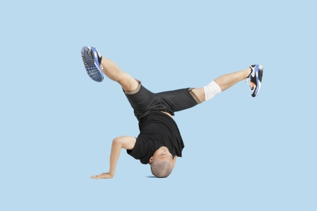 spread legs: Male dancer doing head stand with legs spread apart over blue background