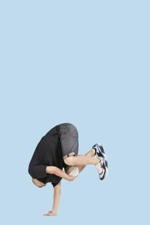 legs apart: Male break dancer balances upside down on one hand over blue background