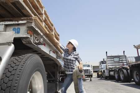 Female industrial worker strapping down wooden planks on logging truck Stock Photo