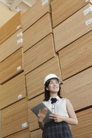 Low angle view of female industrial worker holding tablet PC with stacked wooden planks in background Stock Photo