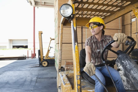 forklift driver: Female industrial worker looking away while driving forklift truck