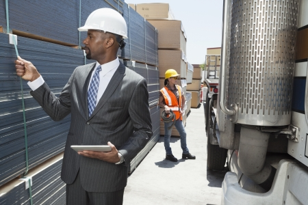 African American male engineer inspecting planks while female worker standing by flatbed truck Stock Photo