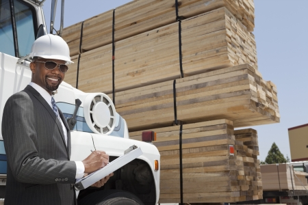 logging truck: Portrait of African American male contractor writing notes while standing by logging truck