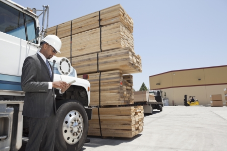 logging truck: African American male contractor using tablet PC while standing by logging truck