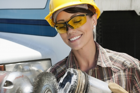 mid adult female: Mid adult female industrial worker buffing a truck engine cylinder LANG_EVOIMAGES