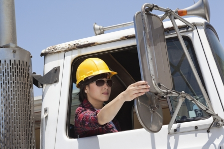 logging truck: Asian female industrial worker adjusting mirror while sitting in logging truck