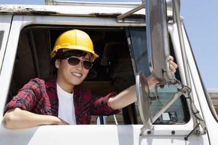 logging truck: Female industrial worker adjusting mirror while sitting in logging truck LANG_EVOIMAGES
