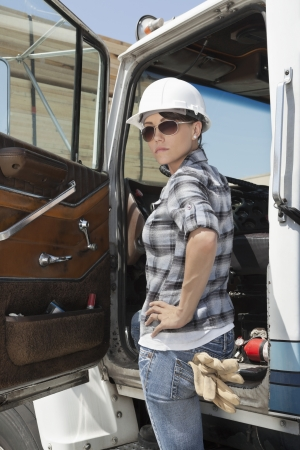 flatbed truck: Confident female industrial worker standing by vehicle door with hand on hip