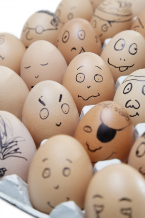 anthropomorphic: Anthropomorphic brown eggs arranged in carton against white background LANG_EVOIMAGES