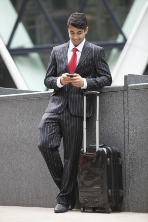 parapet wall: Young Indian businessman with luggage bag using cell phone LANG_EVOIMAGES