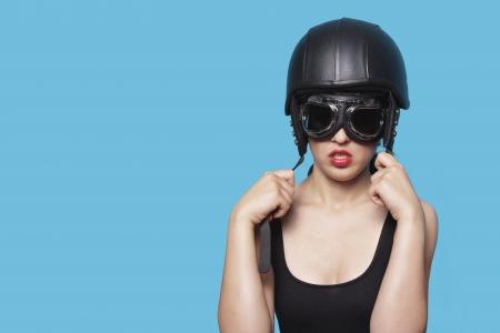 Joven mujer llevaba casco y gafas nostálgico contra el fondo azul