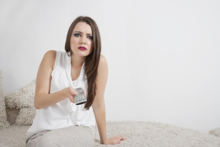 changing channels: Portrait of beautiful young woman holding remote control