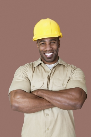 construction worker: Portrait of cheerful young African construction worker over brown background
