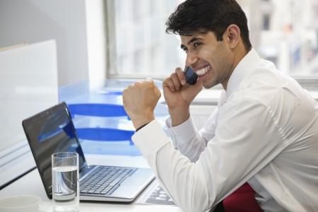 clenching: Excited businessman using cell phone at office desk LANG_EVOIMAGES