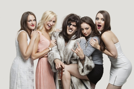 playboy: Young playboy with hand gesture amid happy women over gray background