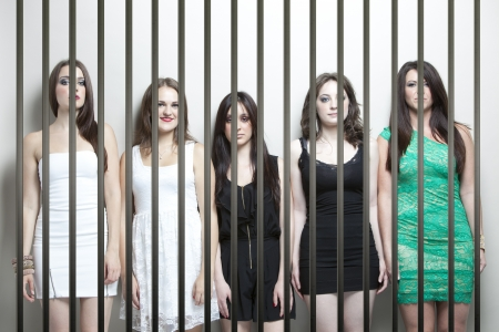 detained: Portrait of five young women standing side by side behinds prison bars