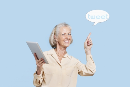 Portrait of senior woman with tablet PC pointing at tweet bubble against blue background Stock Photo - 20769632
