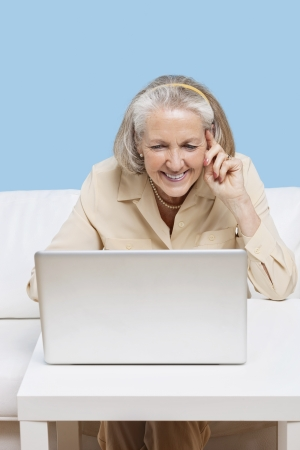 teleconferencing: Cheerful senior woman using laptop for video calling