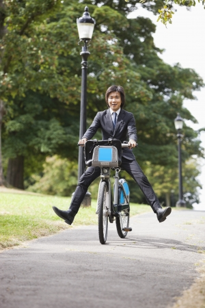 kicked out: Portrait of young businessman riding bicycle with legs kicked out LANG_EVOIMAGES