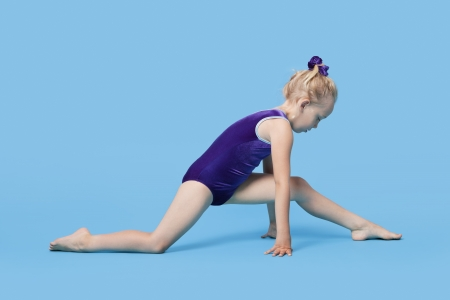 legs apart: Young girl in bodysuit stretching legs over blue background LANG_EVOIMAGES