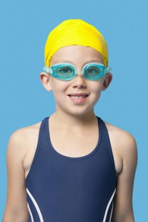 swim goggles: retrato de una joven feliz vistiendo nadar gafas sobre fondo azul LANG_EVOIMAGES