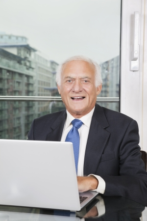 business: Portrait of happy elderly businessman with laptop sitting at table