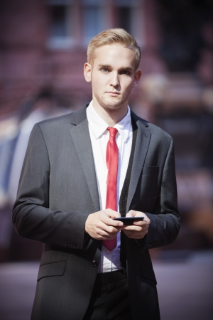 business: Portrait of young businessman holding cell phone