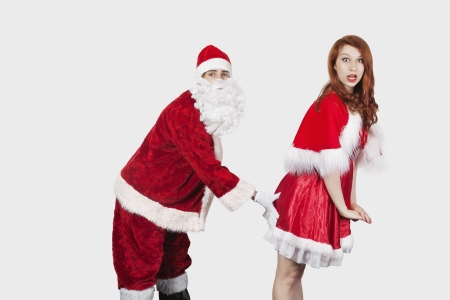 mrs santa claus: Portrait of Santa touching Mrs. Santa inappropriately against gray background