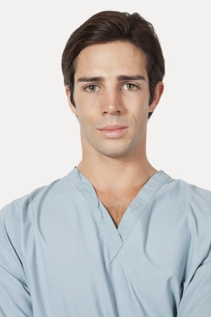 surgical scrubs: Portrait of confident young man in surgical scrubs over gray background LANG_EVOIMAGES
