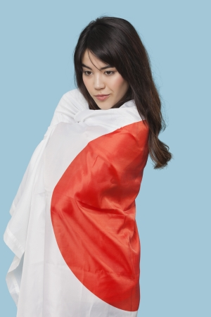 british ethnicity: Patriotic young woman wrapped in Japanese flag over blue background