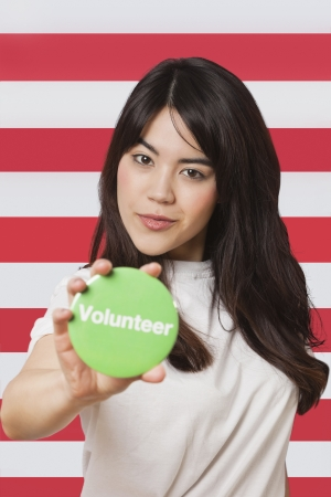 british ethnicity: Portrait of young woman holding out volunteer badge against American flag