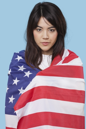 british ethnicity: Patriotic young woman wrapped in American flag over blue background LANG_EVOIMAGES