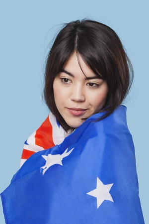 british ethnicity: Patriotic young woman wrapped in Australian flag over blue background