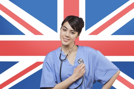 british ethnicity: Portrait of mixed race female surgeon standing over British flag