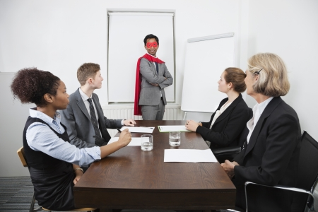 american hero: Business leader as superhero in front of colleagues at meeting in conference room