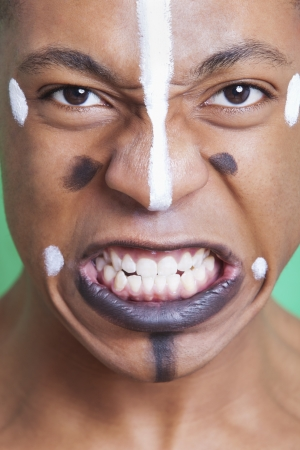 clenching: Detail shot of aggressive mixed race man with painted face clenching teeth LANG_EVOIMAGES